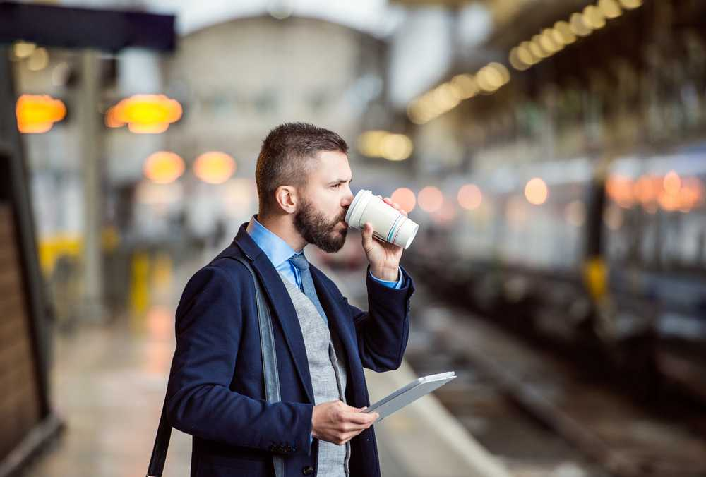 Man sipping a coffee waiting for a train